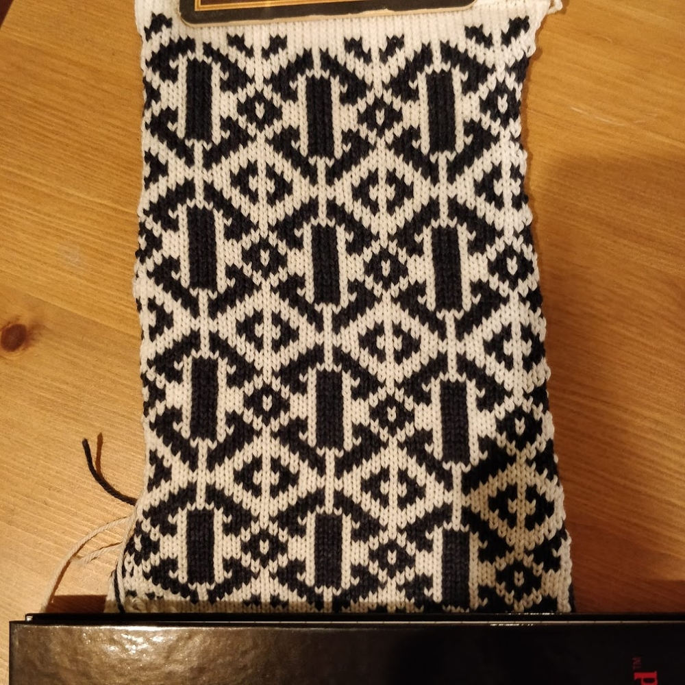A navy and white fair isle swatch with a pattern of diagonal lines surrounding vertical bars.