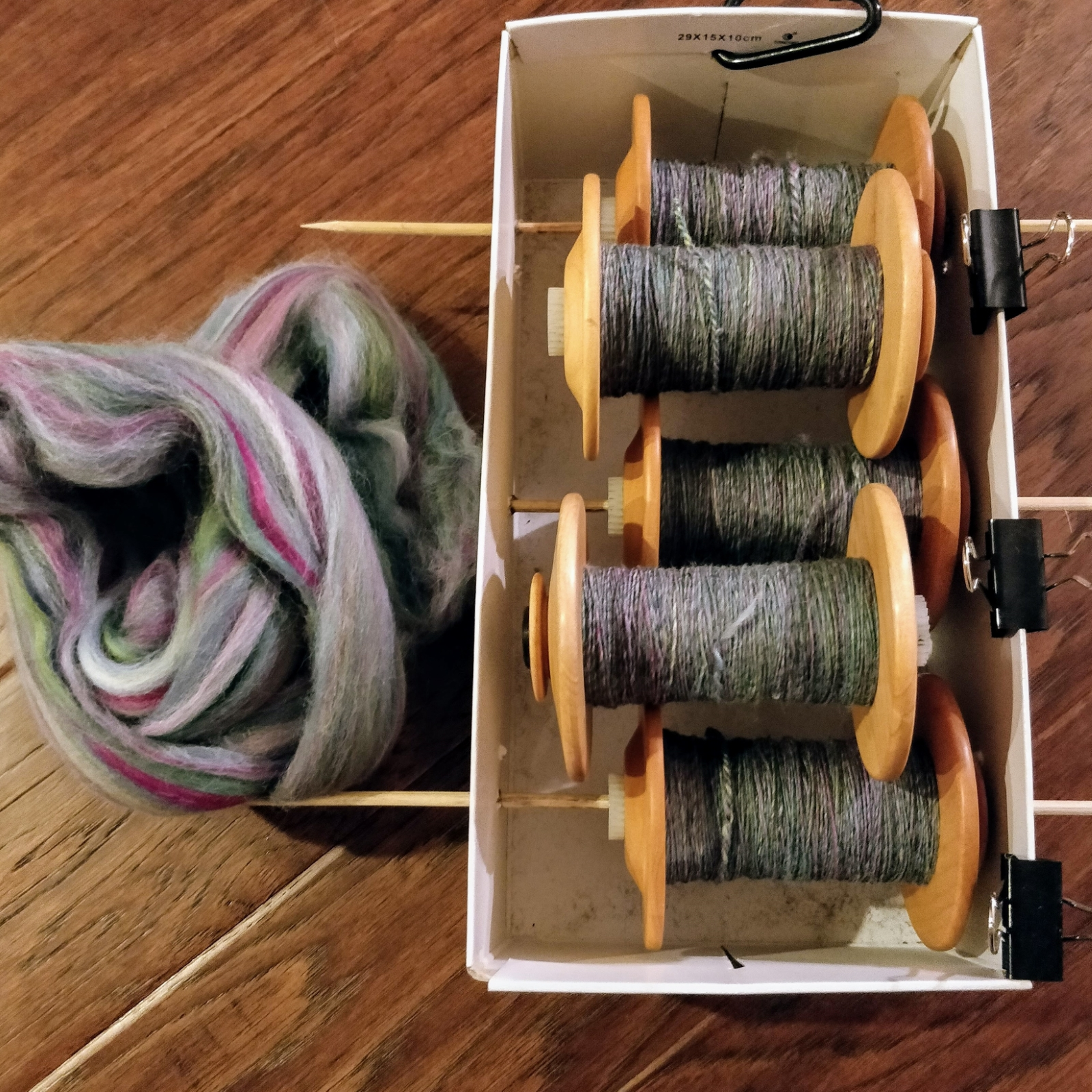 An unspun bit of multi-coloured spinning fibre sits on the floor next to a shoebox with several bobbins of spun singles.