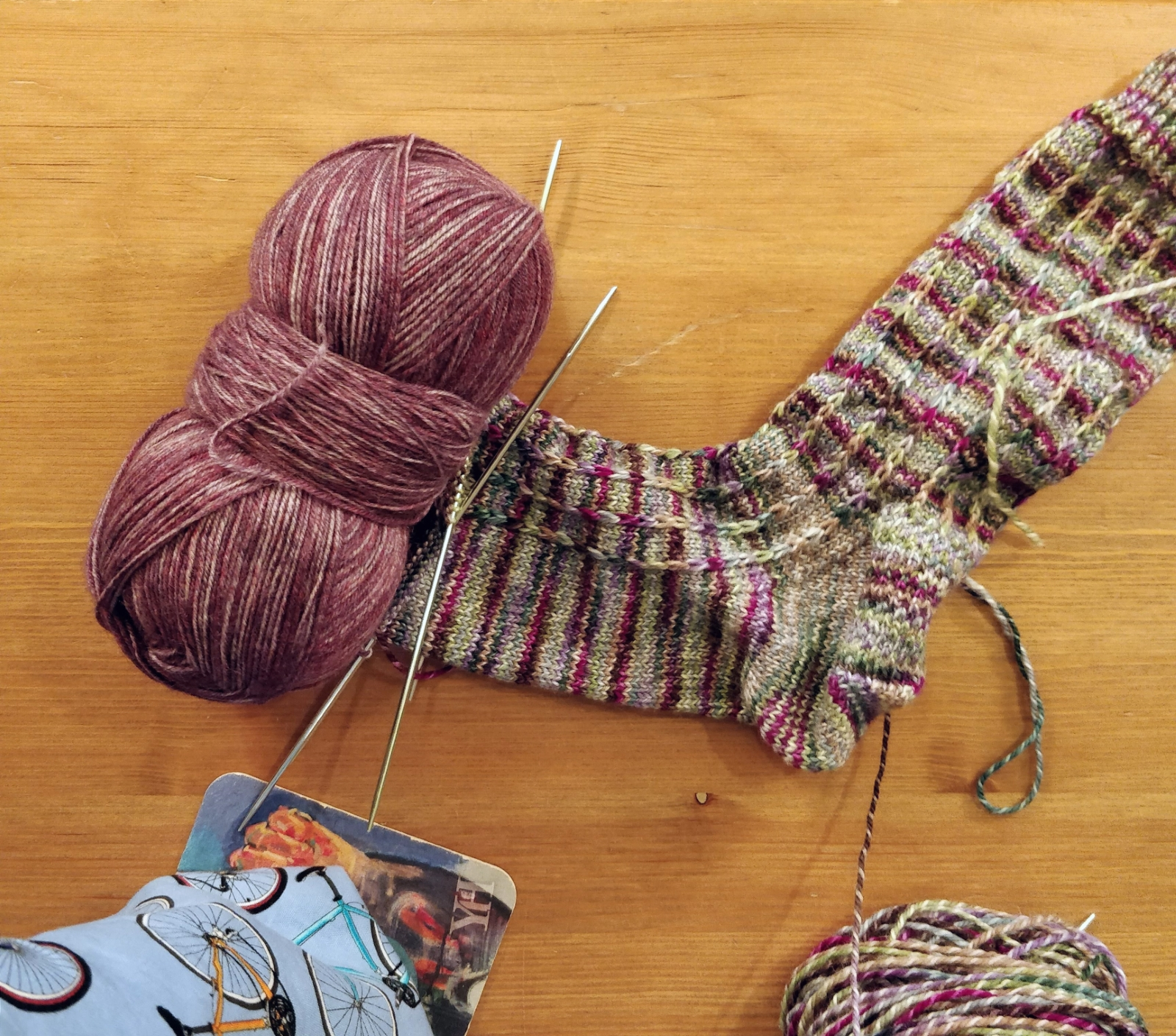 A partially completed sock in variegated shades of pink, green, tan, and blue, with a coordinating ball of pink yarn at the toe.