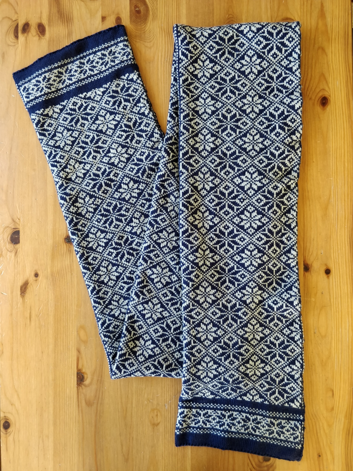 A long scarf with traditional snowflake motifs in navy blue and gray colours.