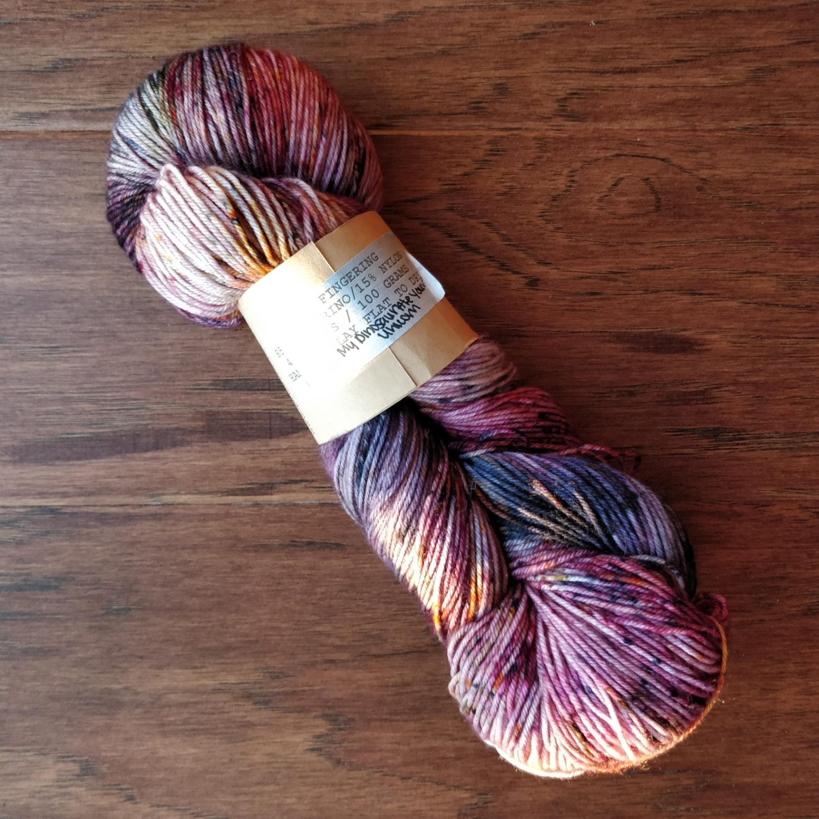 A skein of sock yarn in purples and a bit of orange, very sunsetty colours