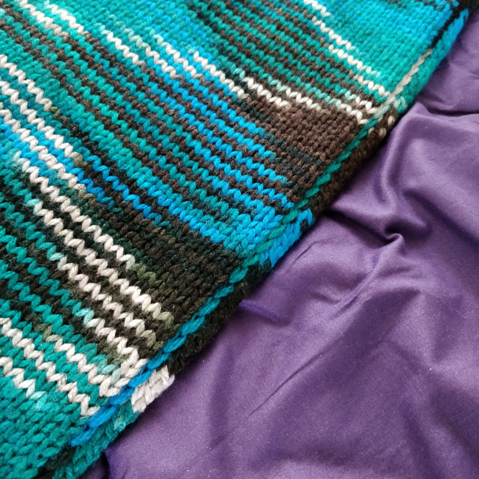 Closeup of the detail of the edge seam of a teal and brown knit wrap.