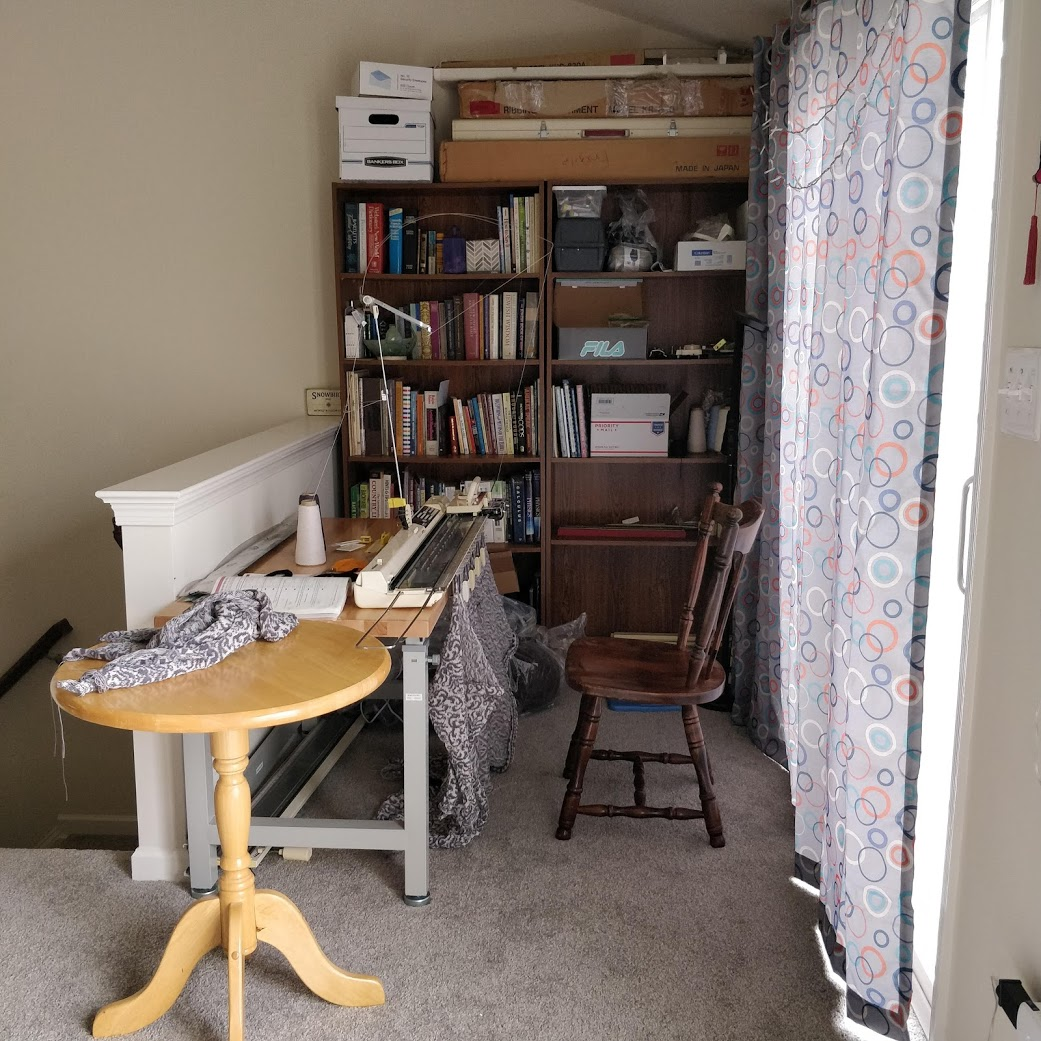 A small nook with a knitting machine, two bookcases, and a sliding glass door covered by a curtain. A stairwell is visible to the left. There is a half-wall between the stairs and the back of the knitting machine's table.