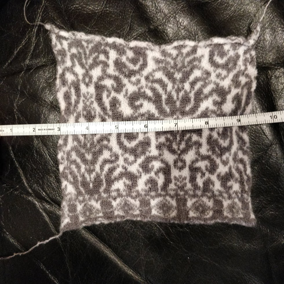 A swatch of the Puppies pattern in purple-gray and white. It looks like damask wallpaper.