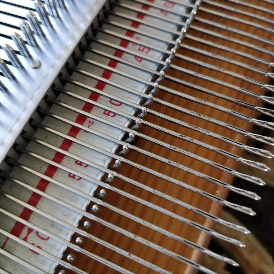 A row of extended knitting machine needles, showing corrosion along their shafts.