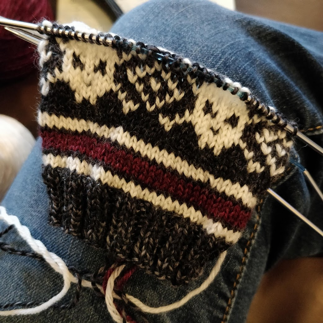 The cuff of a sock with a skull and crossbones motif.