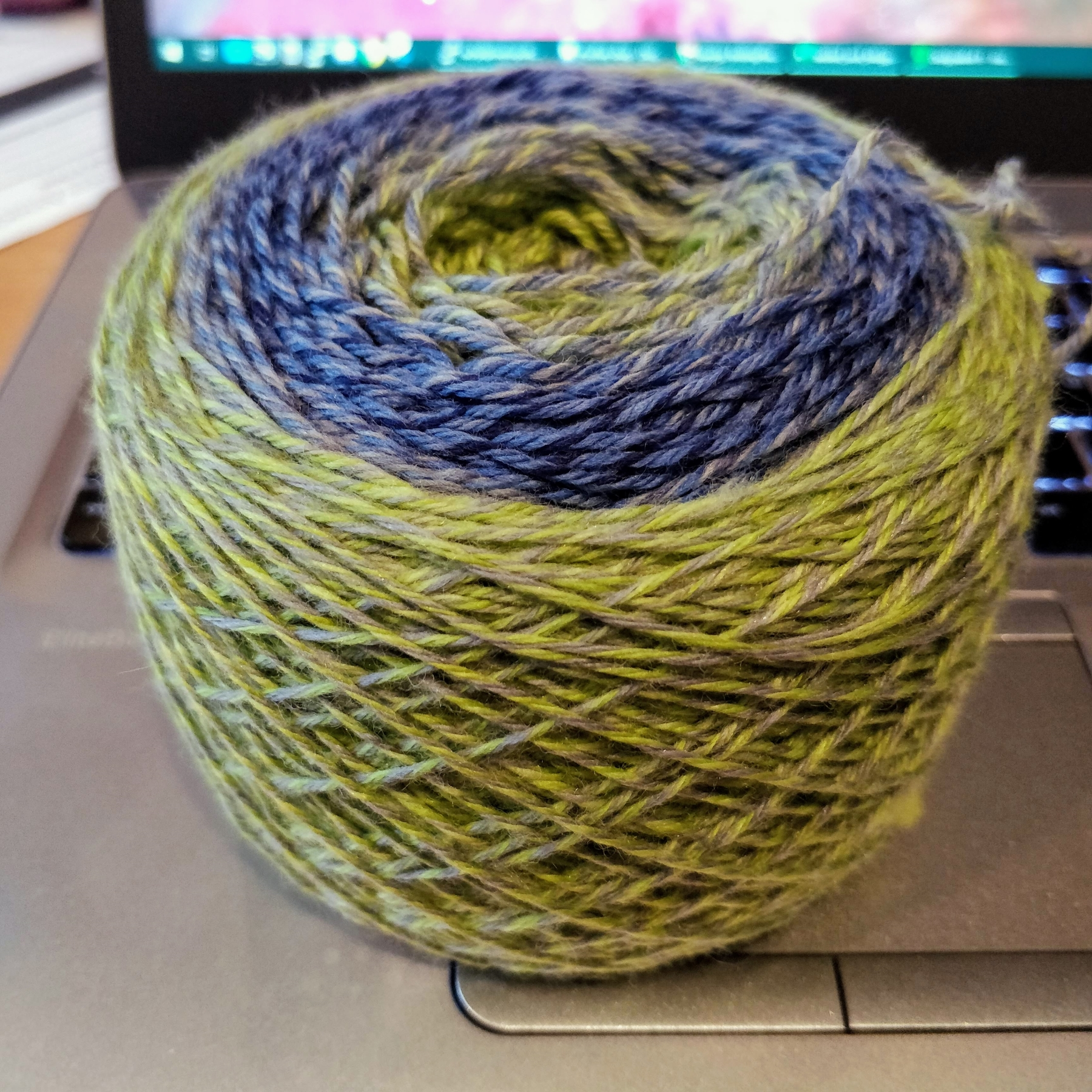 A ball of yarn with the green-blue-green gradient visible on the top edge.