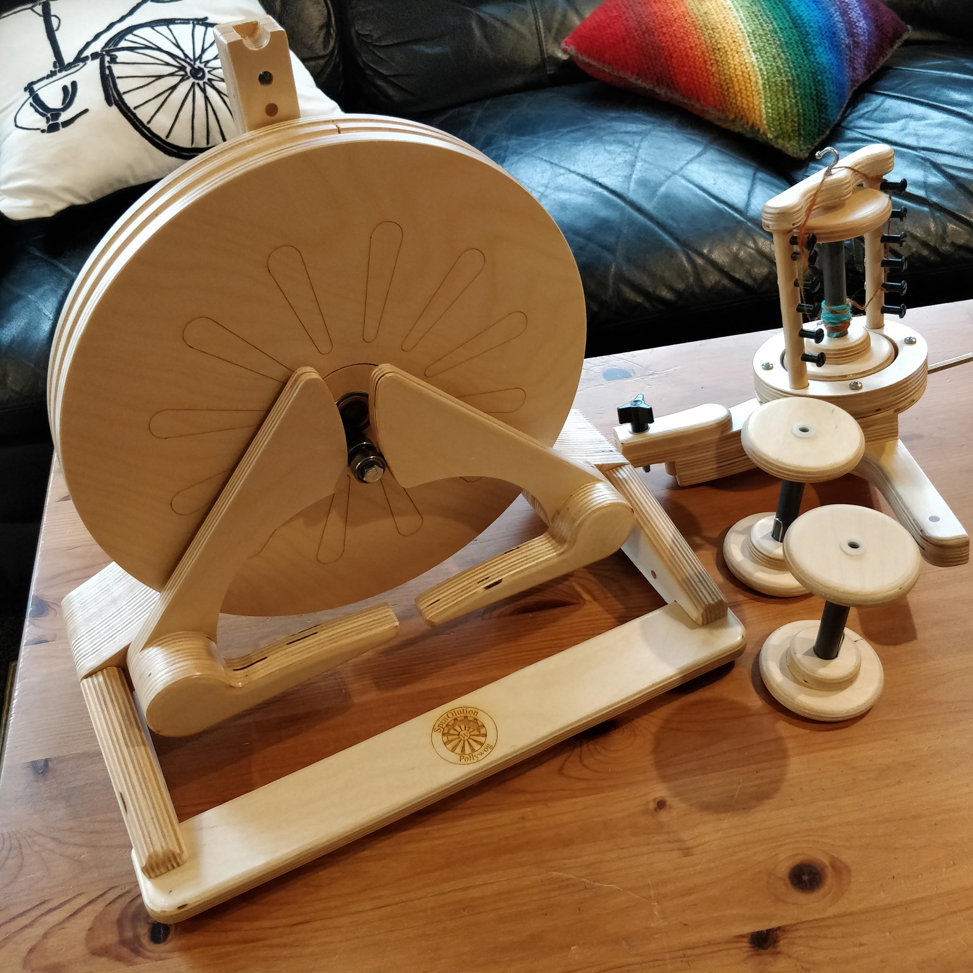 An unassembled Pollywog spinning wheel on a wooden coffee table. The main part of the wheel sits to the left. There are two bobbins next to it, and a third bobbin on the flyer behind them.