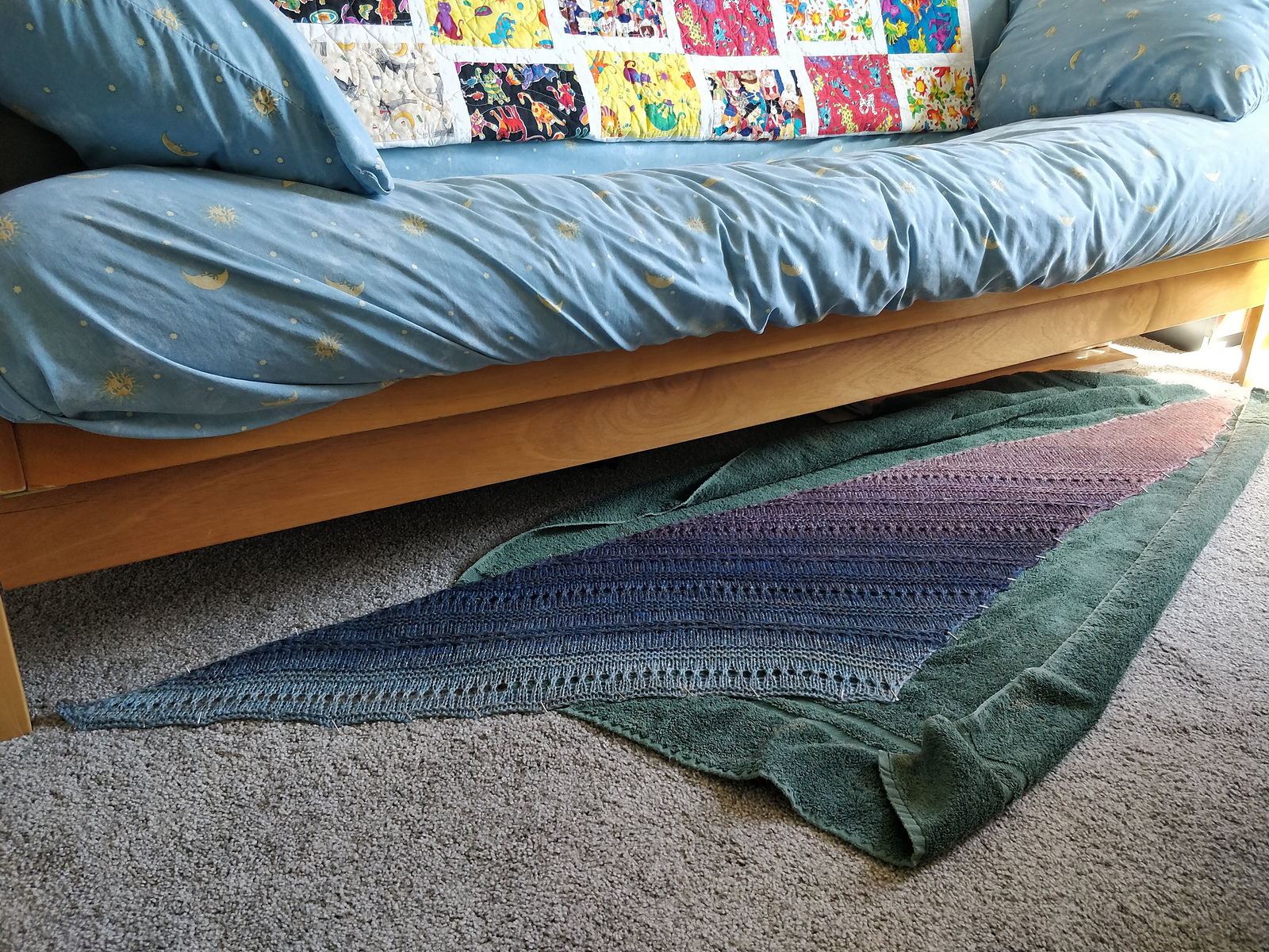 A handknit shawl of handspun yarn is pinned out on a towel on the floor to dry, underneath a futon with moon-and-stars sheets and a quilt hanging on the back. The shawl is a shallow triangle with alternating bands of texture and eyelets. It was knit from one narrow pink end through a gradient of purples and blues to a wide finish of light blue.