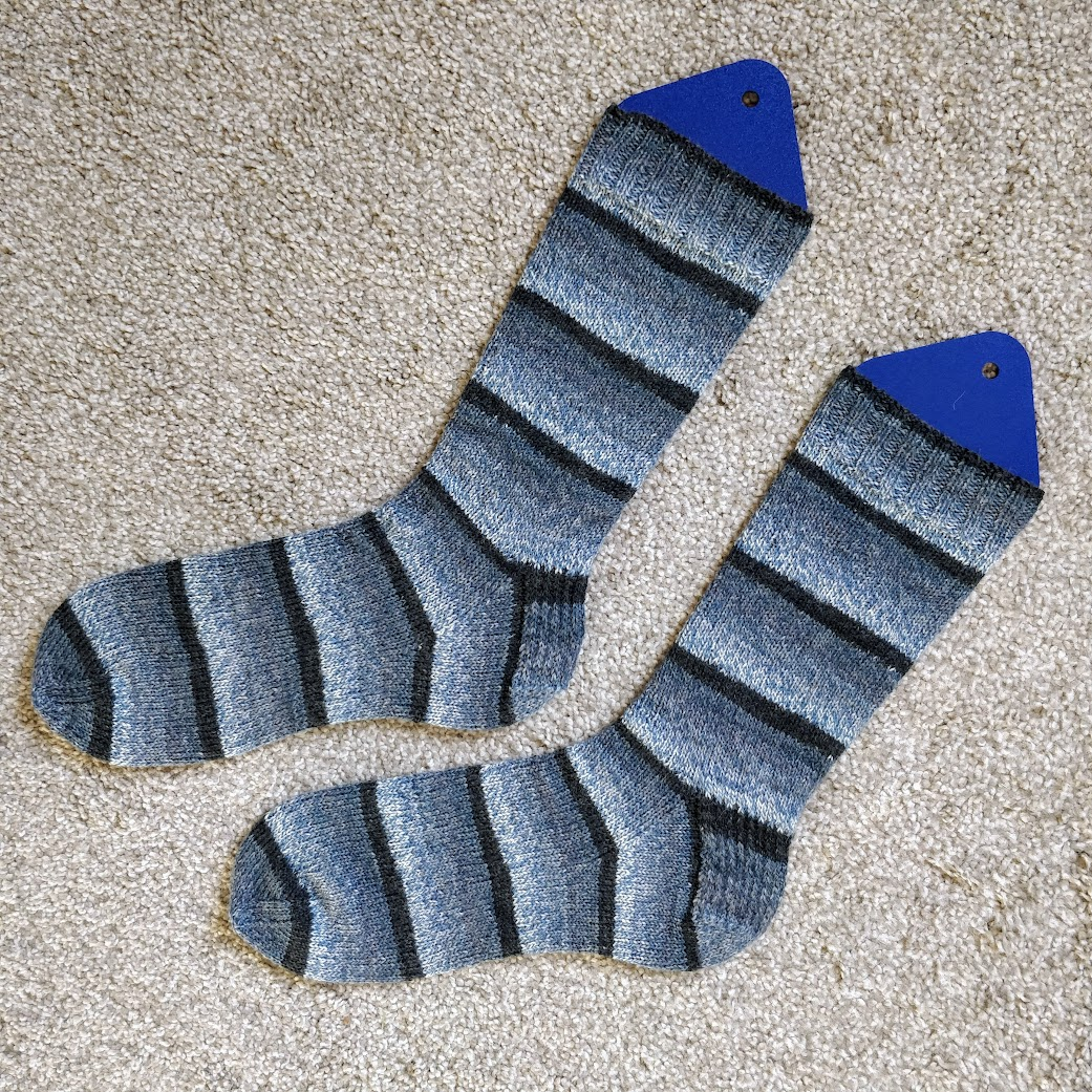 """The """"Got the Blues"""" socks, knit in gradiated shading stripes of dark to light blue."""
