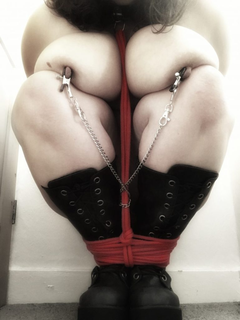 Squatting in platform boots, red rope around my ankles leading to my collar ring, hands behind me, wearing nipple clamps with the connecting chain wrapped around the rope