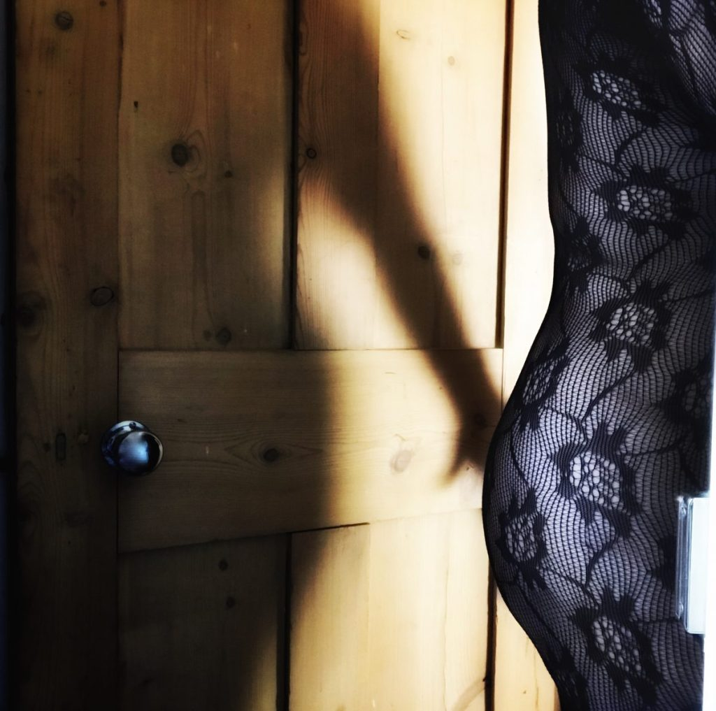Image shows my back and bum at the edge of the door frame, with my shadow on the wooden door behind me, arm outstretched  so that my hand is on my bum. I'm wearing a flowery lace bodystocking