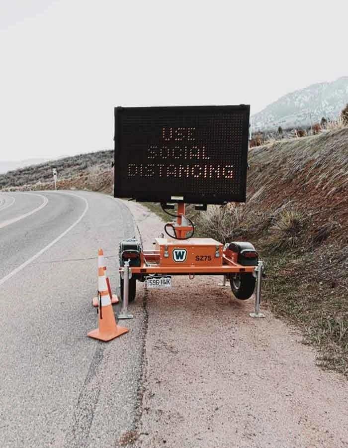 cartellone stradale con su scritto in inglese di mantenere le distanze sociali