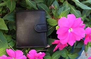 portafoglio nero appoggiato sull'erba e un fiore rosa in primo piano
