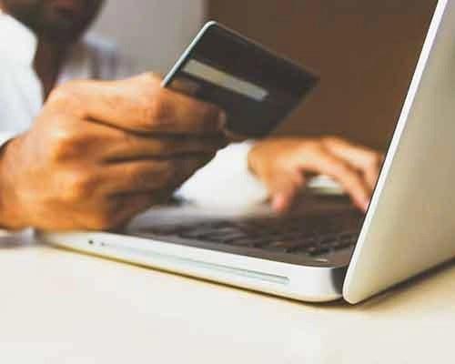 uomo al computer con una carta di credito in mano che sta per acquistare online