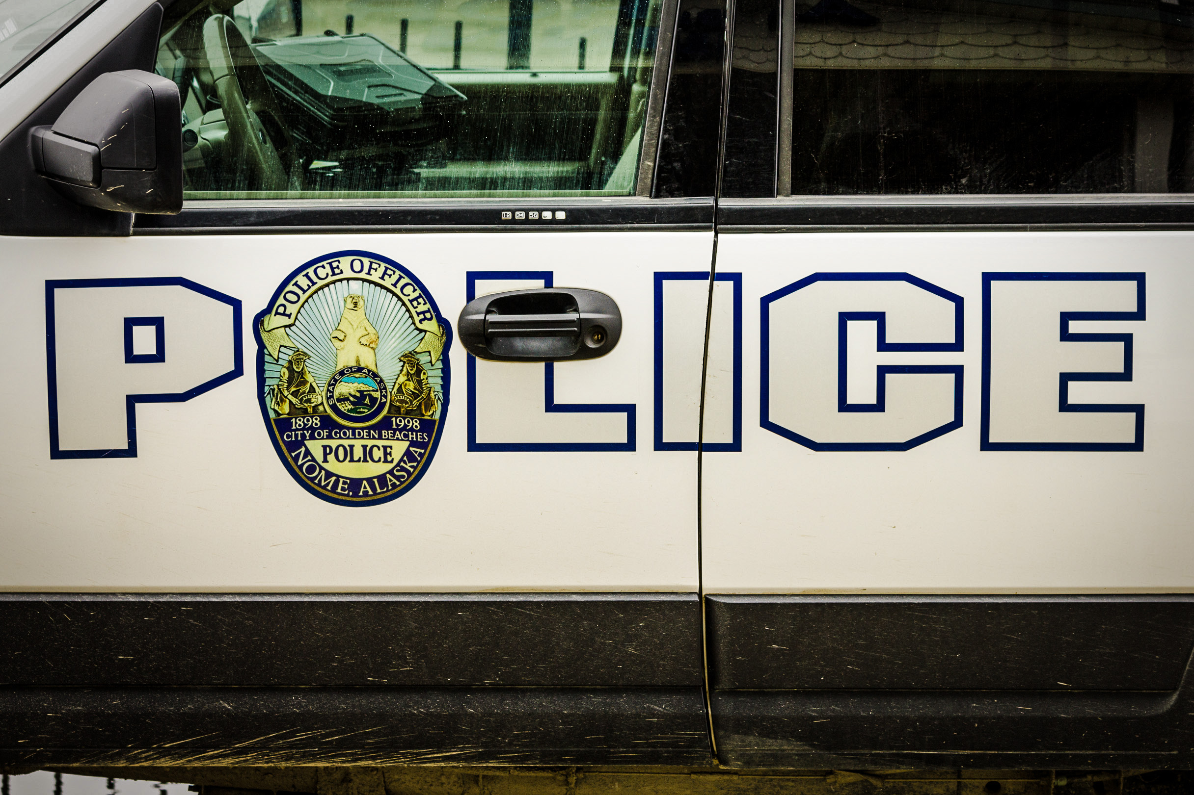 "Block letters spelling ""POLICE"" on the side of a Nome Police Department SUV."