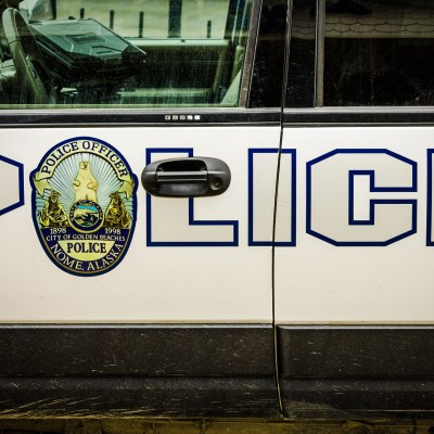 """Block letters spelling """"POLICE"""" on the side of a Nome Police Department SUV."""