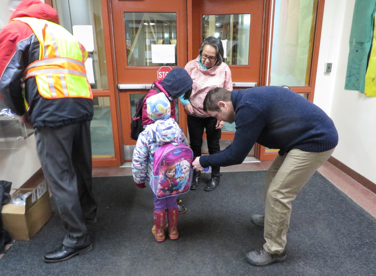 Superintendent Shawn Arnold helps a student attach a reflector keychain to her backpack. Photo: Laura Kraegel, KNOM.