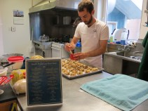 Thomas puts an egg wash on his signature Swedish cinnamon rolls. (Photo: Maddie Winchester, KNOM)