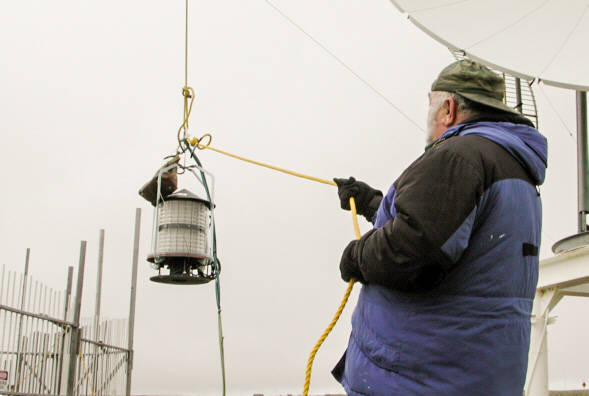 In 2003, Les Brown helps guide the replacement beacon on its 233-foot ascent to the top of the AM tower.