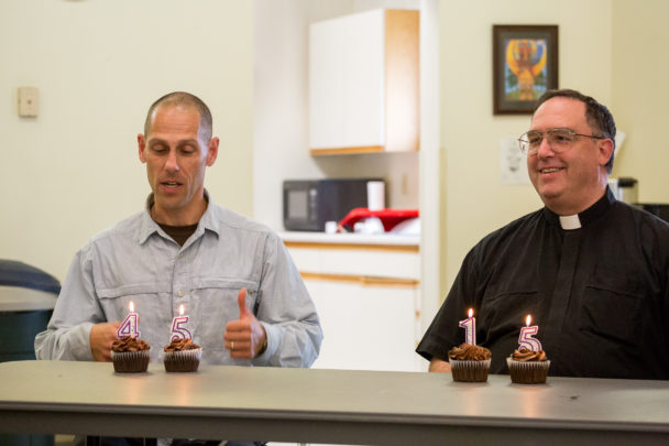 "On KNOM's 45th anniversary, and Father Ross Tozzi's 15th ordination anniversary, KNOM board president Paul Korchin and Father Ross Tozzi pose with cupcakes bearing birthday candles reading ""45"" and ""15,"" respectively."