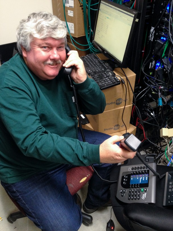 Engineer Joe Mauk helps install KNOM's new telephone system