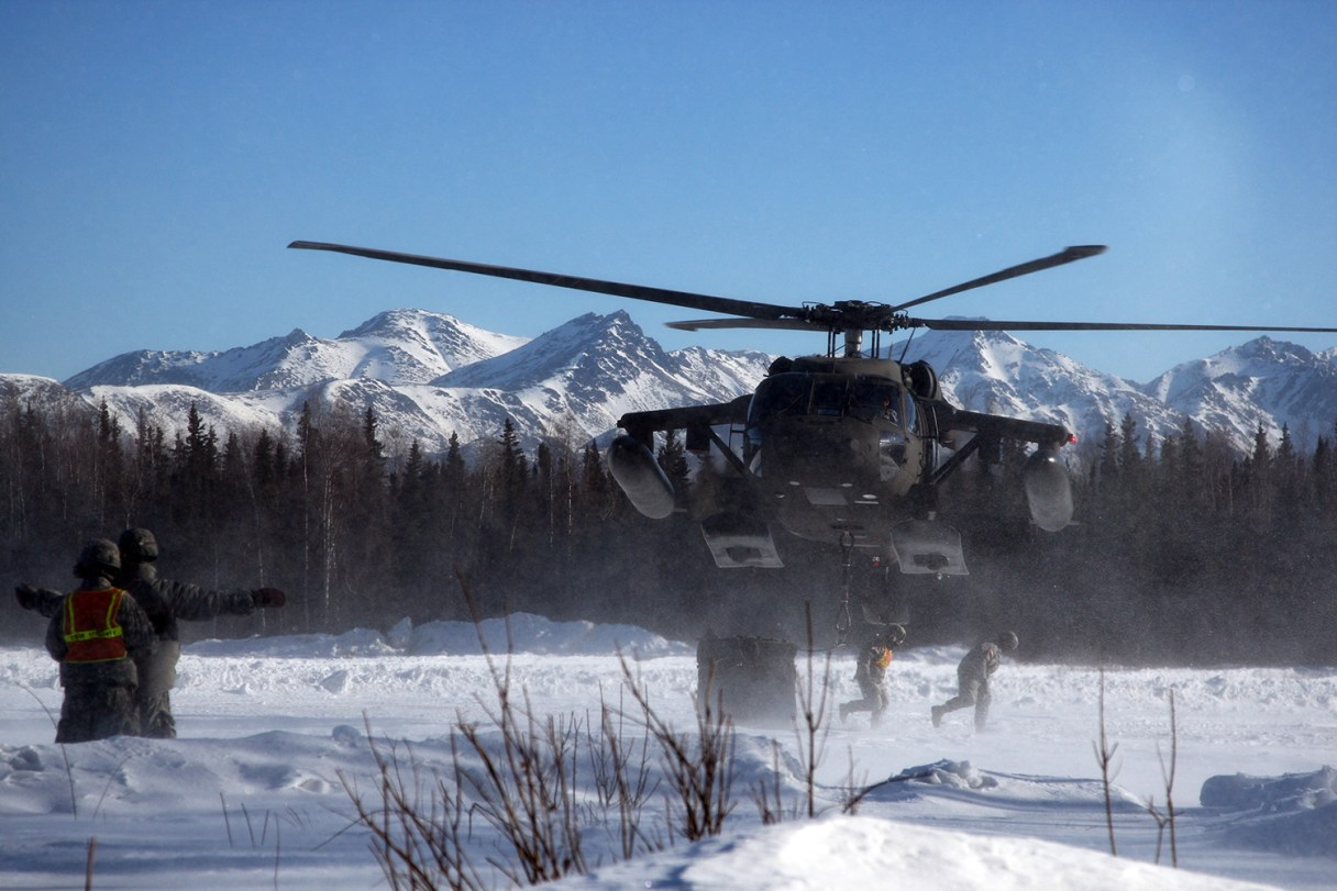 Soldiers clear the landing zone after cargo is secured to a UH-60 Blackhawk helicopter.