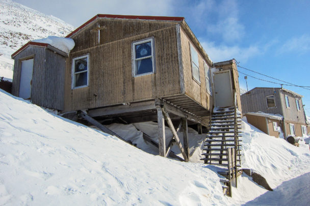 A weather-worn wooden church, perched along a snowy, steep cliff face.