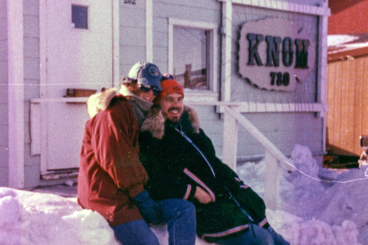 In their volunteer days (circa 1980s), Lynette and Ric Schmidt smile outside the old KNOM station building.
