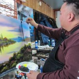 Don Henry painting a tree