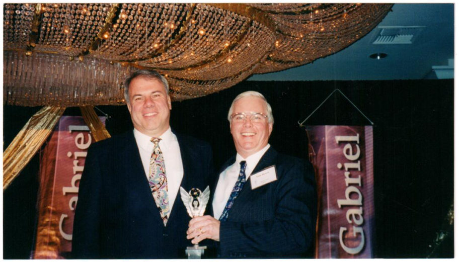 Ric and Tom hold an award statue