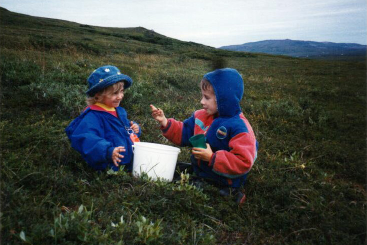 A vintage photo of young children picking berries