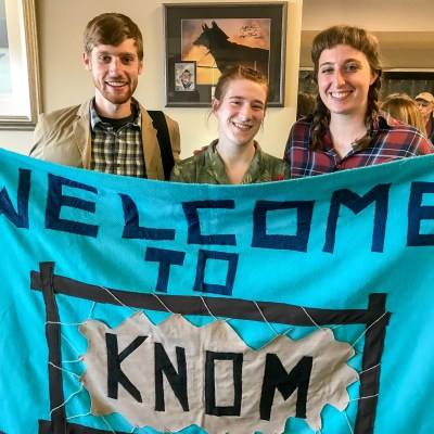 "At the Nome airport: Gabe Colombo, Karen Trop, and Zoe Grueskin holding the ""Welcome to KNOM"" banner that greets newly-arriving volunteers."
