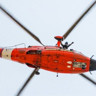Orange and white Coast Guard helicopter flying directly overhead