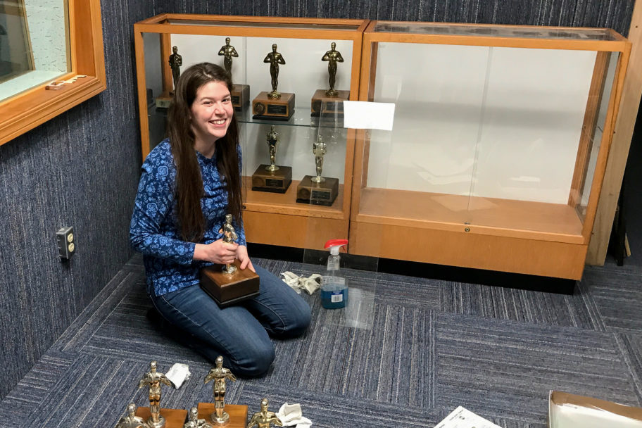 Smiling woman kneels on floor of radio studio, cleaning and organizing shelves of broadcasting awards.