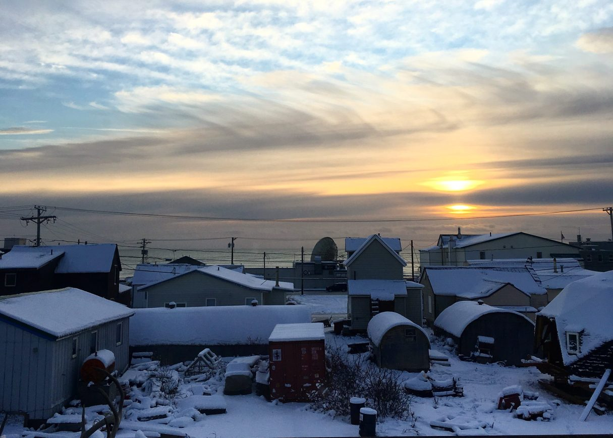 The sun sets over the Bering Sea in the late afternoon. Clouds fill the sky, and snow covers the ground and buildings in Nome