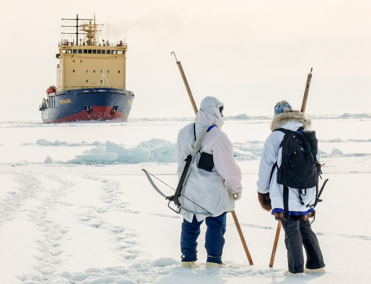 Two people, wearing heavy parkas, hold long poles with iron hooks at the end, standing on sea ice, with a large vessel in the background.