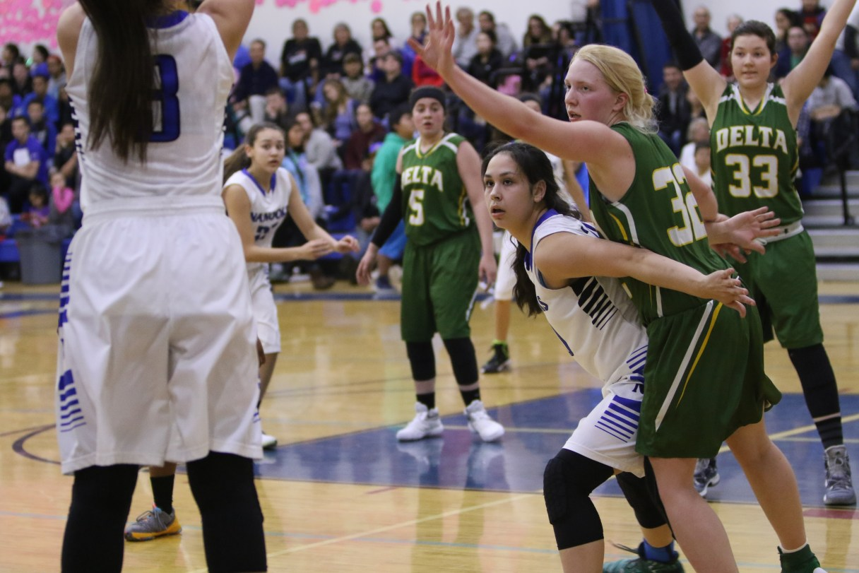 Nanooks girls, in white, play against Delta-Greely, in green, on the Nome-Beltz court