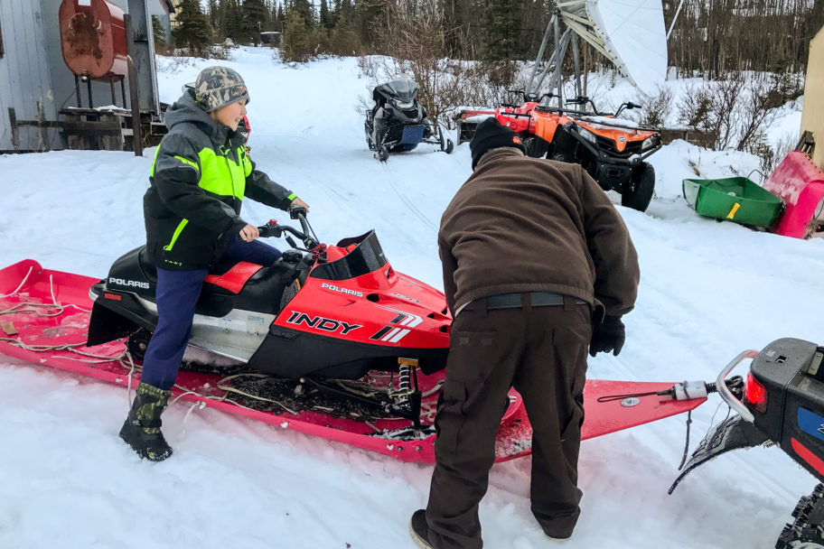 Dan Harrelson assists a child riding a small snowmachine (snowmobile).