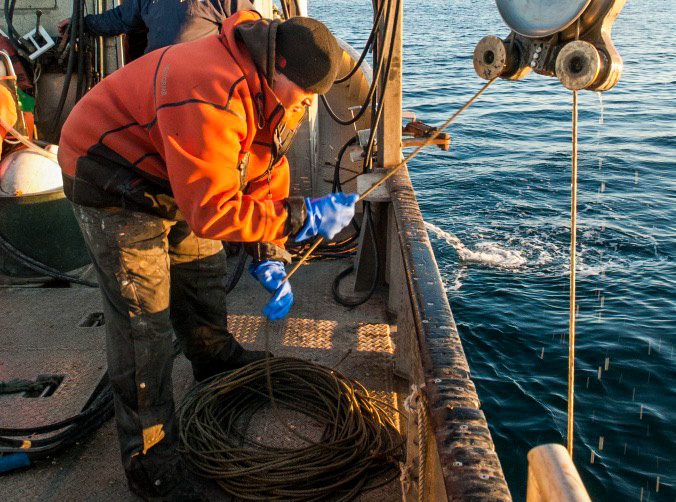 Pulling on a rope, a marine researcher on board a ship hoists an object out of the ocean.