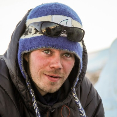 Close-up of musher Joar Leifseth Ulsom, wearing blue hat, sunglasses, black parka
