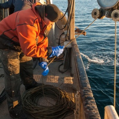 James Longley uses a pulley over the side of a fishing boat to retrieve a sound recorder from the Bering Sea.