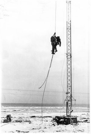 Black-and-white photo of two crew workers dangling from a support cable next to a radio tower near the shoreline of Nome, Alaska.