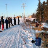 Ambler residents look on as Nicolas Petit gets his dogs settled in straw on the snow at the checkpoint.
