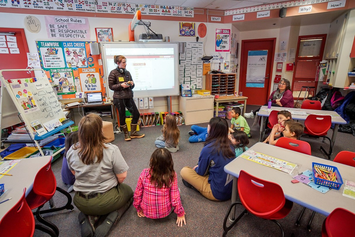 Woman, standing, addresses classroom of elementary school students, their teacher, and a park ranger, all seated.