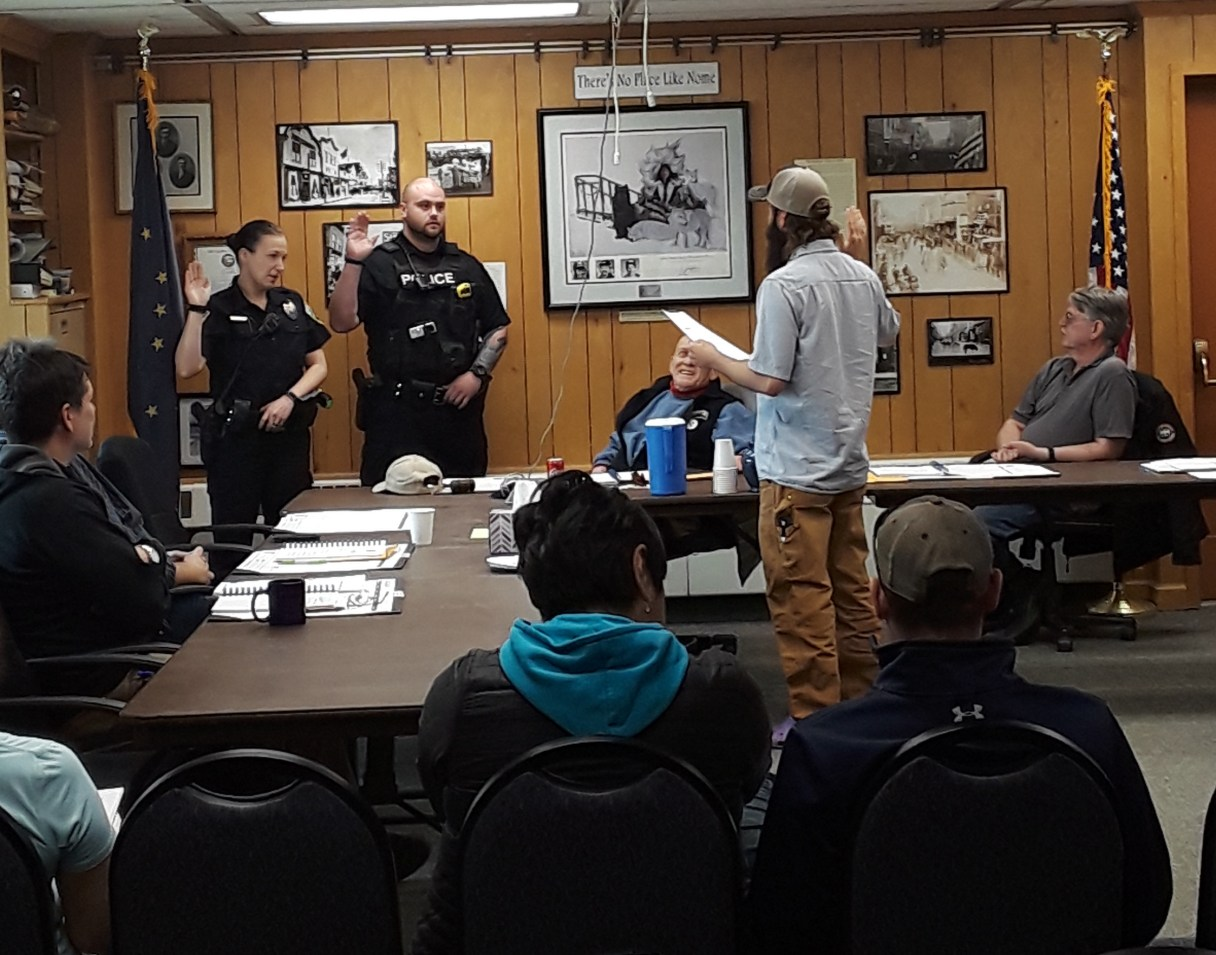 Two NPD officers take their oaths of office, led by City Clerk Bryant Hammond, during a regular City Council meeting. Photo Credit: Davis Hovey, KNOM (2018)