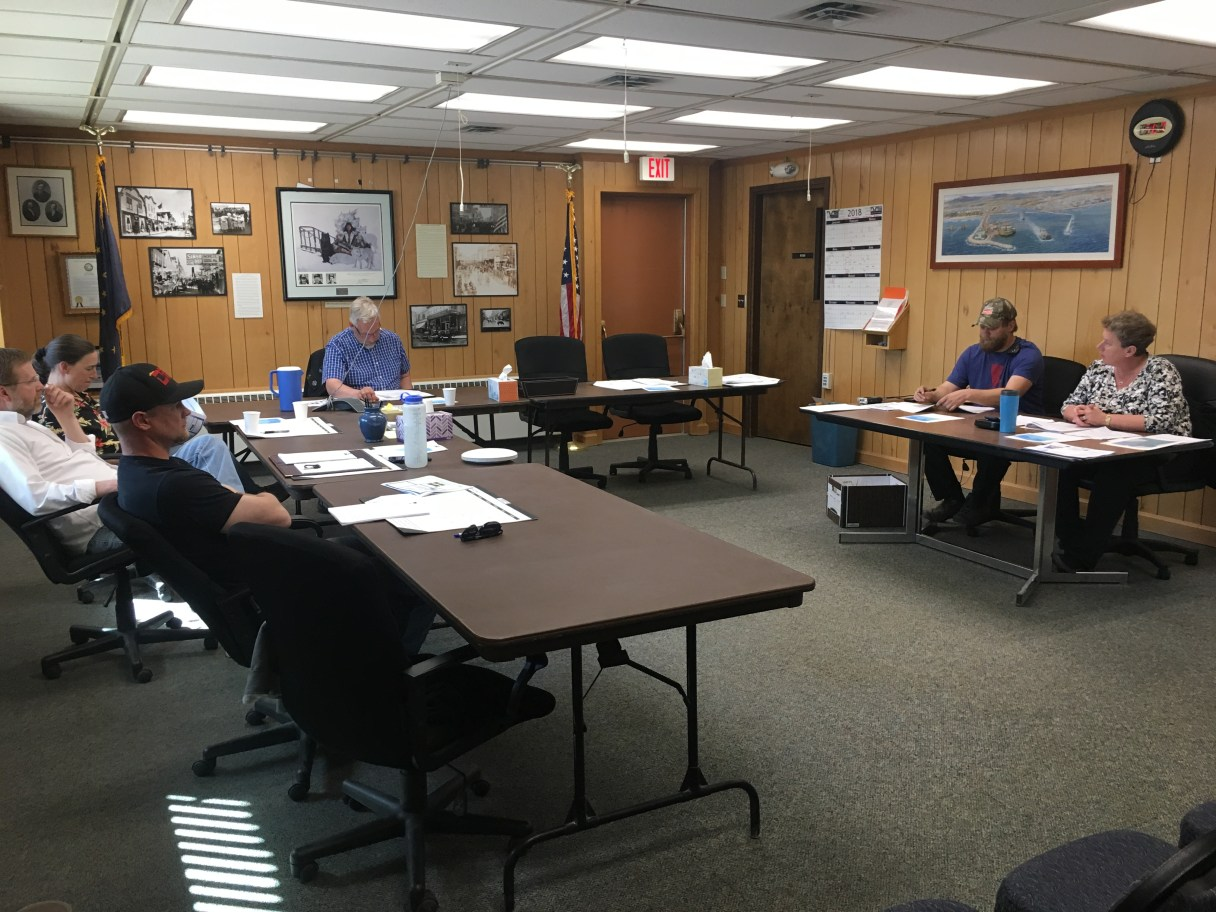 The Nome Port Commission sits around a semi-circle of tables in Council Chambers for their June meeting.
