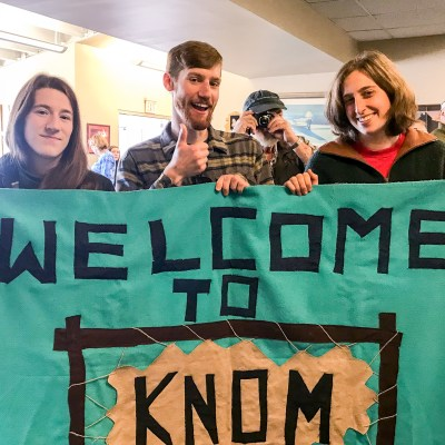 "Three people hold a teal ""Welcome to KNOM"" banner inside a small airport terminal, while a man, standing over their shoulder, holds his own small camera back at the photographer."