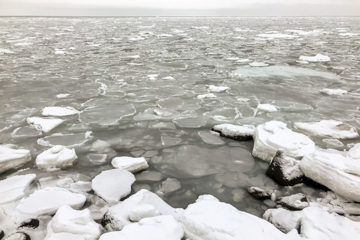 Scattered patches of thin sea ice as seen from the shoreline on a wintry day in a rural Alaska village.