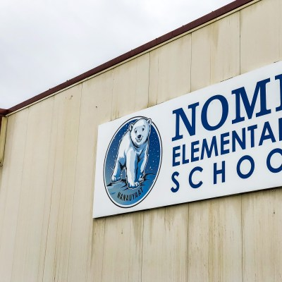 Exterior of Nome Elementary School, an off-white building with a smiling polar bear as its mascot.